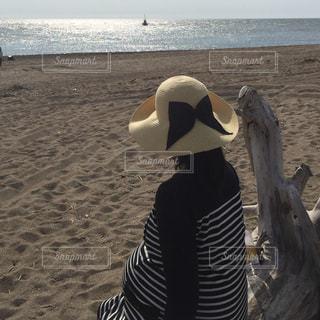 砂浜で座っている女性の写真・画像素材[886848]