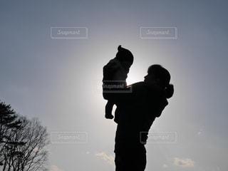 夕焼けの前に立っている人の写真・画像素材[2390534]