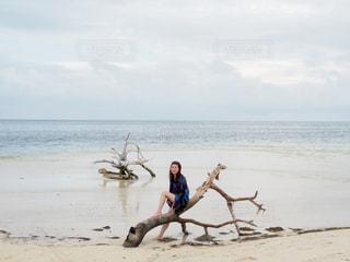 水の体の近くのビーチに立っている人の写真・画像素材[1281754]