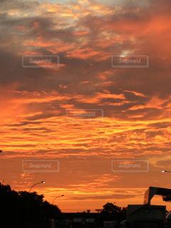日没時に都市の上空を飛ぶ飛行機の写真・画像素材[2455324]