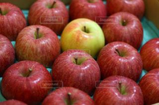 木製のまな板の上に座っている赤いりんごの写真・画像素材[906919]