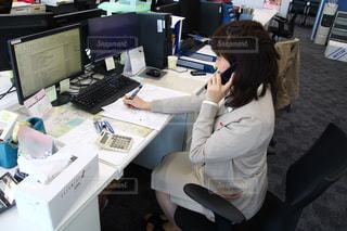 コンピューターの前で机に座っている人の写真・画像素材[932526]