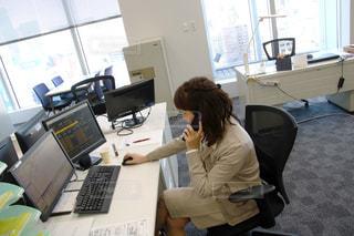 ラップトップ コンピューターを使用してテーブルに座っている女性の写真・画像素材[932529]