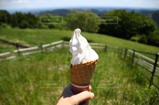 フェンスの前でアイス クリーム コーンを持っている手の写真・画像素材[1197146]