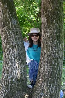 木の隣に立っている人の写真・画像素材[1198772]