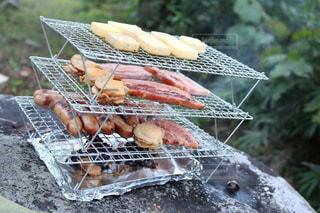 近くのグリルの上に食べ物をの写真・画像素材[1203630]