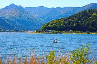 背景の山と水の体中の小型船の写真・画像素材[1217561]