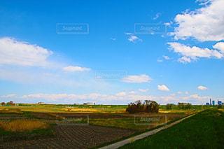 空の雲と大規模なグリーン フィールドの写真・画像素材[1217583]