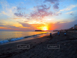 ビーチでの背景の夕日に人々 のグループの写真・画像素材[1268605]