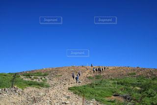 芝生の丘の上を歩く人々 のグループの写真・画像素材[1404644]