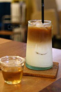 近くのテーブルの上のガラスのコップで飲み物をの写真・画像素材[1411648]