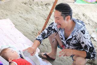 砂浜の上に座っている男の写真・画像素材[1426072]