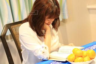 テーブルの上に座っている女性の写真・画像素材[1545820]