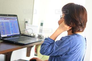 ラップトップ コンピューターを使用してテーブルに座っている人の写真・画像素材[1560541]