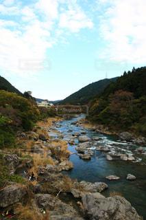 山の中腹に木と岩の多い川の写真・画像素材[1597610]