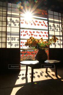 暗い部屋でテーブルに座っている人々 のグループの写真・画像素材[1634954]