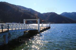 背景の山が付いている水の体の上の橋の写真・画像素材[1639874]