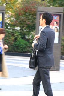 身に着けているスーツとネクタイは、携帯電話で話す人の写真・画像素材[1645279]