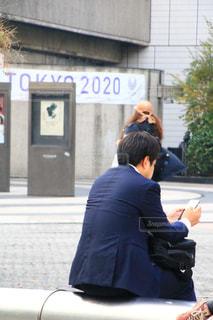 携帯電話で話している建物の前に立っている男の写真・画像素材[1645280]