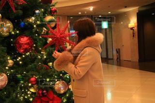 クリスマス ツリーの前に立っている人の写真・画像素材[1673442]