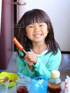 小さな女の子のテーブルに座っての写真・画像素材[854898]