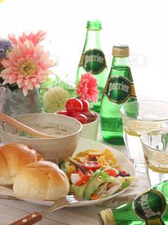 ボトル入りワインとテーブルの上に食べ物のボウルの写真・画像素材[905906]