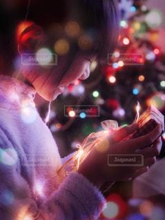 携帯電話を持っている人のぼやけた画像の写真・画像素材[940971]