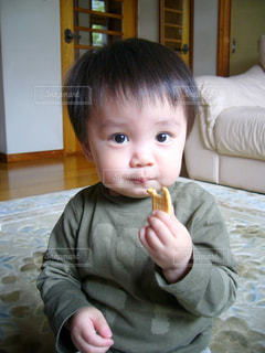 ベッドの上に座っている小さな男の子の写真・画像素材[1046771]