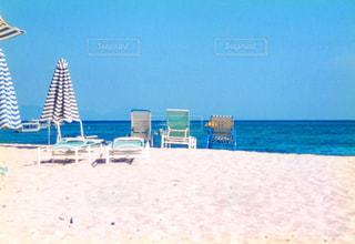 砂浜の上に座って傘の写真・画像素材[1219883]