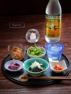 ボトル入りワインとテーブルの上に食べ物のボウルの写真・画像素材[1269314]