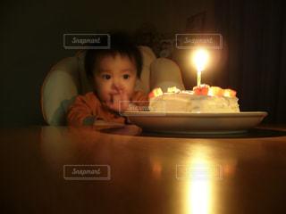 キャンドルとバースデー ケーキの前に座っている小さな子供の写真・画像素材[1686661]