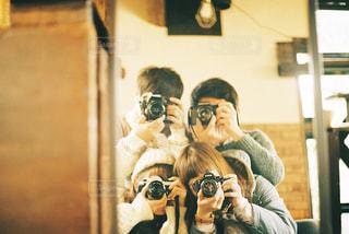 カメラにポーズ鏡の前に立っている人の写真・画像素材[1870395]