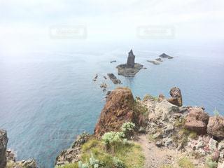 水の体の横に岩が多い区域の人々 のグループの写真・画像素材[885243]