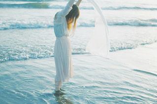 水の体の横に立っている人の写真・画像素材[776619]