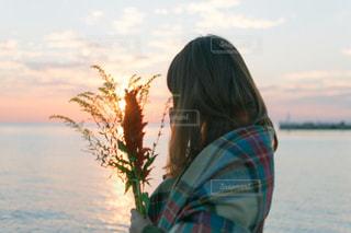水の体の前で立っている女性の写真・画像素材[872635]