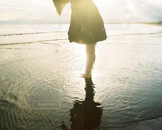 水の体の横に立っている人の写真・画像素材[1233976]