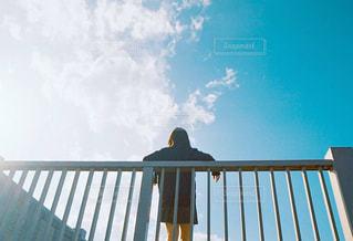 フェンスの前にあるベンチに座っている人の写真・画像素材[1233977]
