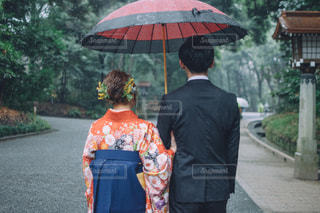 傘を持って雨の中で立っている人の写真・画像素材[1604385]