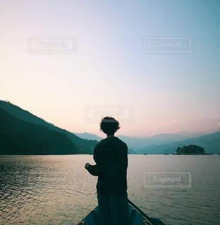水の体の前に立っている男の写真・画像素材[1604389]