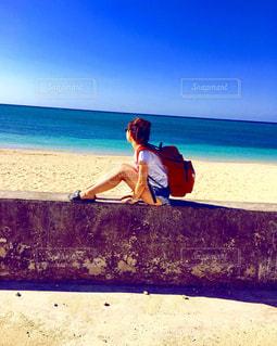 ビーチに座っている男の写真・画像素材[907255]
