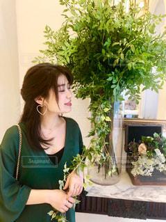 テーブルの上に花の花瓶の隣に立っている女性の写真・画像素材[2101047]