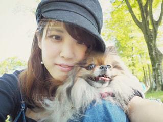 カメラにポーズ犬と帽子を身に着けている女の子の写真・画像素材[874085]