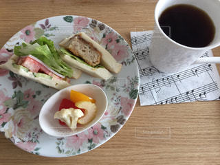 食べ物の皿と一杯のコーヒーを木製のテーブルに置いての写真・画像素材[3273756]