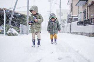 雪の中に立っている小さな男の子の写真・画像素材[4226108]