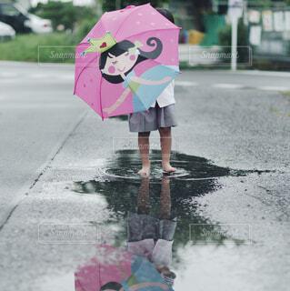 ピンクの傘を持って通りを歩いている小さな女の子の写真・画像素材[4585203]