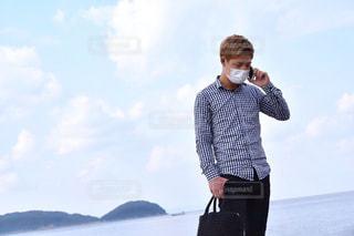 水の前に立っている男の写真・画像素材[1063677]