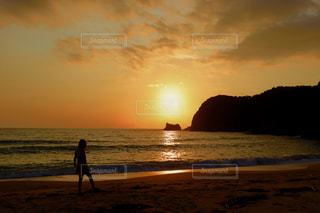 海の横にあるビーチに沈む夕日の写真・画像素材[959045]