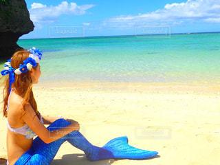 水の体の近くのビーチに座っている女性 - No.897098
