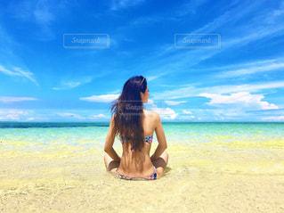 水の体の近くの浜辺に立っている男の写真・画像素材[2131956]