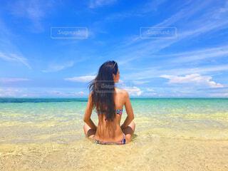水の体の近くのビーチに立っている男の写真・画像素材[4468196]